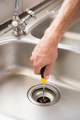 Man fixing sink with screwdriver at home in the kitchen