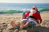 pic of christmas claus  - Santa Claus relaxing in his lounge chair on a tropical sandy beach  - JPG