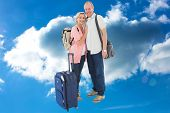 Smiling older couple going on their holidays against cloudy sky