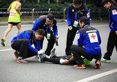 Medical support help a injured marathon runner's legs on the street