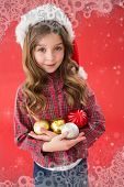 Festive little girl smiling at camera holding baubles against snowflake frame