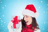 Astonished brunette in santa hat showing gift against blue vignette