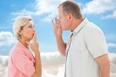 Older couple holding hands to mouth for silence against cloudy sky