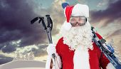Happy santa posing with ski and ski poles against snowy landscape with fir trees