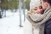Young female in winterwear with her boyfriend near by