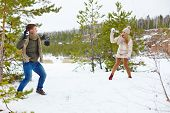 Young guy and his girlfriend throwing snowballs at one another in the forest