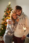 Happy young guy and girl celebrating xmas or New Year together