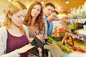 Embarrassed woman looking for money in her wallet at supermarket checkout