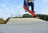 foto of skateboarding  - skateboarder legs skateboarding at outdoor skatepark ramp - JPG