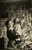 GERMANY, DECEMBER 25, 1938: Mother with a little daughter near Christmas tree