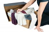 pic of partially clothed  - Cardboard with various packed and unpacked garments and partial view of a woman who inspects the goods isolated - JPG