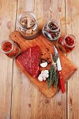 image of flesh  - fresh raw beef meat fillet flesh with peppercorn and thyme ready to grill on wood figured old style board  over table with spices in glass - JPG