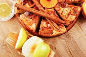 baked food : apple pie served with fresh apples, raw lemon and mandarin,  tea cup on wooden plate over table