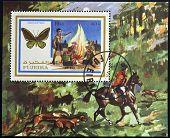 FUJEIRA - CIRCA 1972: A stamp printed in Fujeira shows boy scouts and ornithoptera circa 1972