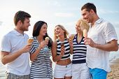 summer, holidays, sea, tourism and people concept - group of smiling friends eating ice cream and talking on beach