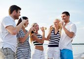 summer, holidays, tourism, drinks and people concept - group of smiling friends with bottles drinking beer or cider on beach