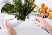 Woman Affixing Branches On Christmas Wreath