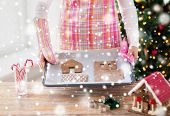holidays, christmas, baking and sweets concept - closeup of woman holding pan with gingerbread house details on it at home