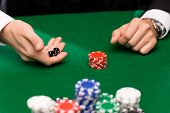 casino, gambling, poker, people and entertainment concept - close up of poker player with dice and chips at green casino table
