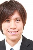 portrait of young Japanese man smiles on white background