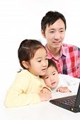 father and children on laptop computer
