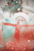 Cute little girl sitting in giant christmas gift against light design over floor boards
