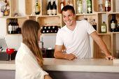 Barman Smiling At Female Customer