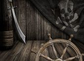 stock photo of saber  - Pirates ship steering wheel with old jolly roger flag and saber - JPG