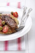 image of plum tomato  - potato pancake with smoked mackerel green olive plum tomato and crushed pepper on a plate - JPG