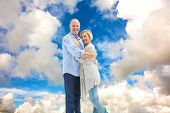 Happy mature couple hugging and smiling against blue sky with white clouds