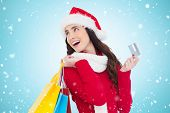 Festive brunette holding shopping bags and credit card against blue vignette