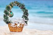 Basket with Christmas decorations on a beach at the region of the sea