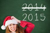 Festive stressed redhead holding gifts against green chalkboard