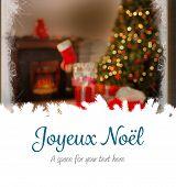 Joyeux noel against christmas home seen through frosty window