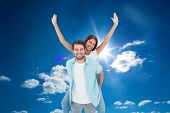 Happy casual man giving pretty girlfriend piggy back against cloudy sky with sunshine