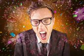 Young angry businessman shouting at camera against colourful fireworks exploding on black background
