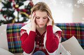 Pretty blonde woman having a headache on the sofa against snowflakes