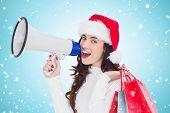 Festive brunette holding gift bags and megaphone against blue vignette