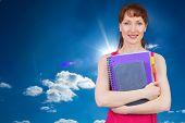 Woman holding her school notebooks against cloudy sky with sunshine