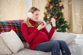 Pregnant woman looking at baby shoes sitting on sofa against twinkling stars