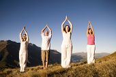 Group of people doing yoga on the mountains.