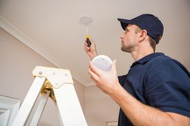 foto of handyman  - Handyman installing smoke detector with screwdriver on the ceiling - JPG