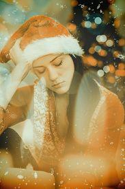 stock photo of sad christmas  - Festive brunette feeling sad at christmas against candle burning against festive background - JPG