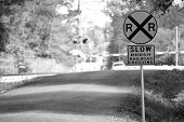 stock photo of cross  - Black and white photo of a railroad crossing sign on a rural road with railroad crossing in the background - JPG