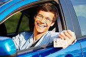 pic of car-window  - Happy young man in glasses showing his driving license from open car window - JPG