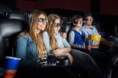 picture of watching movie  - Family of four with snacks watching 3D movie in cinema theater - JPG