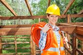 pic of timber  - Portrait of happy female construction worker holding pipe and hammer in timber cabin at site - JPG