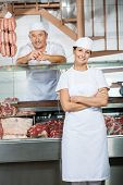 foto of slaughterhouse  - Portrait of male and female butchers at display cabinet in butchery - JPG