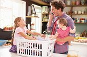 image of laundry  - Father Using Mobile Phone As He Sorts Laundry With Children - JPG
