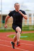 foto of race track  - healthy man run on athletics race sport track and representing concept of sport and speed